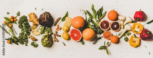 Fototapeta Variety of immunity boosting foods. Flat-lay of ginger, turmeric, kale, artichoke, citrus fruit, herbs, garlic, pepper over white background, top view. Healthy, raw vegan virus defeating ingredients obraz