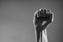 Cropped Hand Clenching Fist Against Gray Background