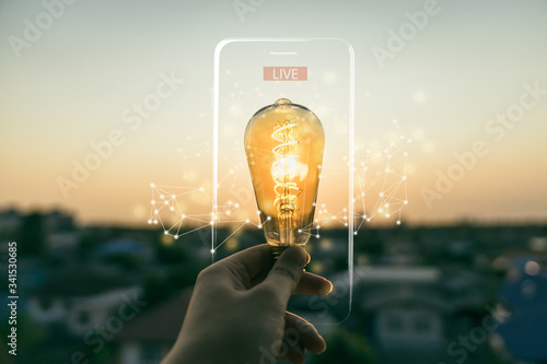 Fotografia Hand business man holding light bulb with lighting frame of mobile phone and Live text