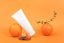 White Blank Cosmetic Bottle, Tube Of Cream, Lotion For Body, Face Or Hand, Orange Fruit And Green Branch Eucalypt. Concept Cosmetics With Vitamin C, Antioxidants Or Anti-cellulite. Mockup Front View