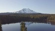 Volcano Mount Adams at Sunrise with Smooth Lake Reflection. Washington State, Great Northwest, United States of America. Mountain lake with turquoise water and green trees. Beautiful spring landscape