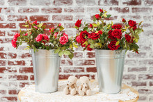 Red Maroon Roses In A Metal Galvanized Pot. Artificial Fake Rose Flowers Decor In A Bucket On A Brick Wall Background. Roses In Pots And Two Small Bears On The Garden Table Decoration Valentine's Day