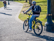 Cyclists Man And Woman Ride Bicycles Along The Park Path Towards Each Other
