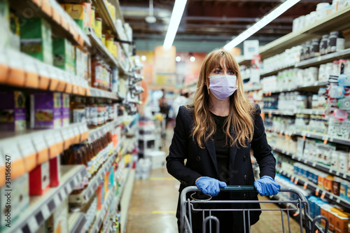 Woman in a face mask wearing latex gloves while shopping in a supermarket during Wallpaper Mural