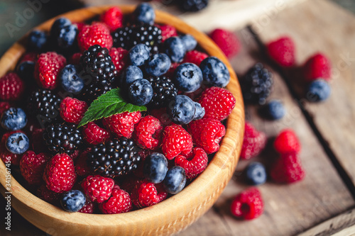 фотография blueberries and raspberries, blackberry in a wooden bowl on old wood background