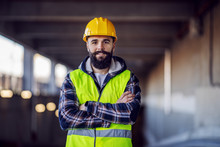 Cute Caucasian Bearded Construction Worker With Safety Helmet On Head In Vest Standing With Arms Crossed At Construction Site And Looking At Camera.