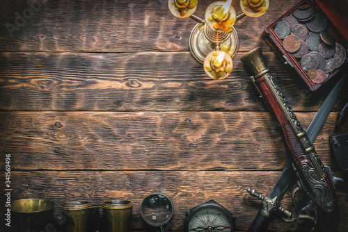 Fotografie, Obraz Pirate treasure chest with ancient coins and other various pirate equipment on flat lay table background