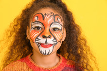 Funny African-American Girl With Face Painting On Color Background