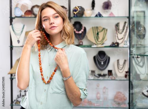 Valokuva Girl trying on cornelian stone necklace