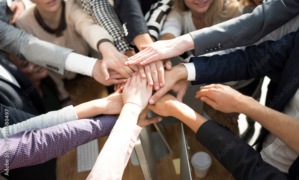 Fototapeta close up. group of young business people putting their palms together.