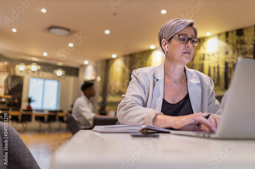 Fotomural Female Caucasian Entrepreneur working remotely on laptop in cafe