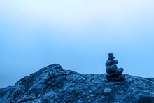 Minimalism. A Small Cairn Stands On A Large Boulder With Dense Fog In The Background. Blue Tinting In Color 2020. Horizontal.