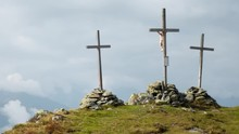 Timelapse Of Three Large Crucifixes On Top Of A Mountain. Timelapse Showing Three Large Christian Crosses Being Held By Large Stone Piles At The Peak Of A Mountain During A Cloudy Day