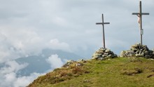 Timelapse Zoom In Of Three Large Crucifixes On Top Of A Mountain. Timelapse Showing Three Large Christian Crosses Being Held By Large Stone Piles At The Peak Of A Mountain During A Cloudy Day
