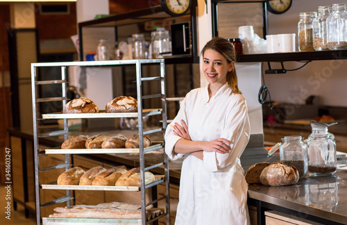 Papel de parede Portrait of young female baker standing at bakery.