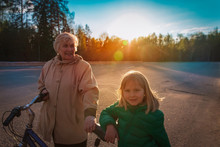 Happy Active Grandmother With Little Granddaughter On Bike Ride