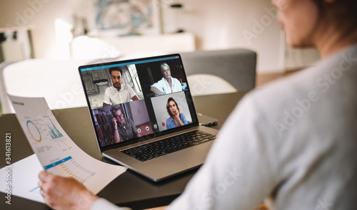 Obraz Woman discussing business with team over a video conference - fototapety do salonu