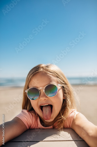 Fotografia Playful girl at the beach sticking out her tongue