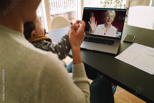 Fotografie, Tablou Woman having a video call with her mother