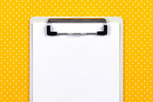 Clipboard With Blank Paper Sheet On Vibrant Yellow Polka Dot Background. Top View. Close-up. Copy Space.