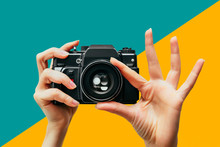 Vintage Camera In Female Hand. A Photo. Photographer. Manual Focus. Colored Background.