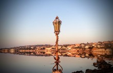 Old Lamp Post By River Against Sky