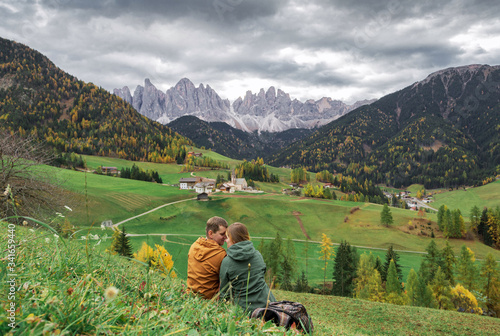 couple in love in Santa Maddalena village with Dolomites mountains in background Wallpaper Mural