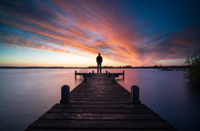Man Standing On A Jetty Looking Over A Lake During A Colorful Dawn.