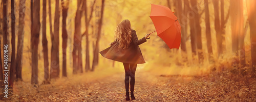 Obraz young woman dancing in an autumn park with an umbrella, spinning and holding an umbrella, autumn walk in a yellow October park - fototapety do salonu