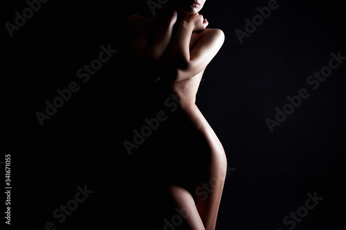 Obraz Nude Woman silhouette under light in the dark - fototapety do salonu