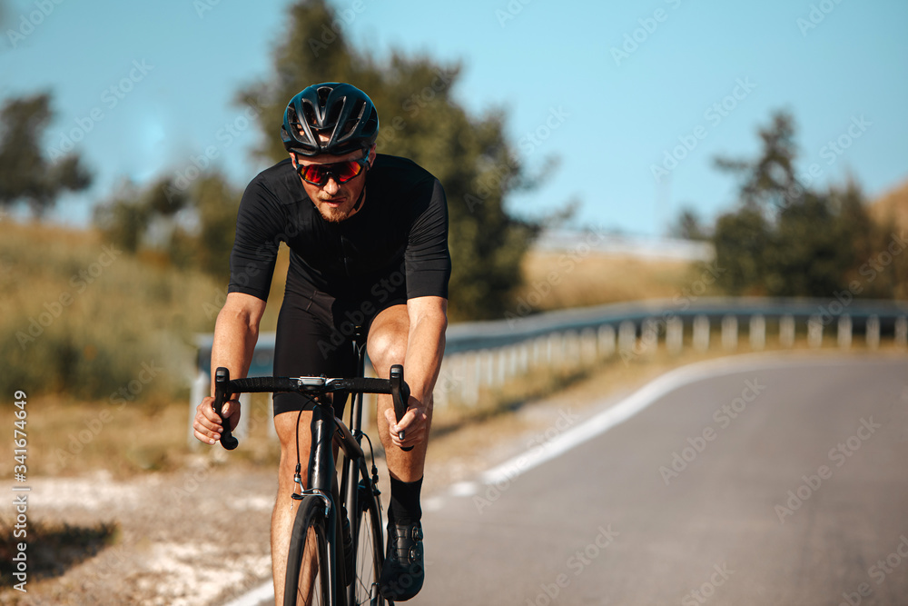 Fototapeta Front view of professional cyclist in sport outfit practising in cycling with blur background of green nature. Concept of summer activity and healthy lifestyle