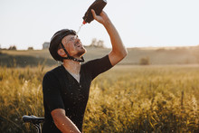 Mature Tired Athlete In Sportswear And Protective Helmet Splashing Cold Water On His Face From Black Bottle After Riding Bike During Sunny Days. Bearded Man Refreshing After Workout Outdoors.