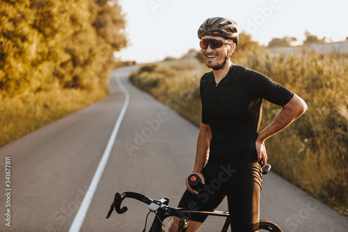 Canvas Print Cheerful bearded man in activewear, black helmet and sport glasses sitting on bike and looking on camera with beautiful nature around
