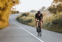 Professional Male Cyclist In Black Helmet, Protective Glasses And Activewear Dynamically Riding Bicycle On Paved Road With Blur Background. Concept Of Summer Activity And Healthy Lifestyle