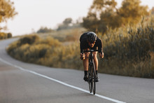 Professional Sporty Cyclist In Black Helmet, Protective Glasses And Active Wear Dynamically Riding Bicycle In A Half-bent Pose For Better Speed. Man Preparing For Competitions And Races On Fresh Air