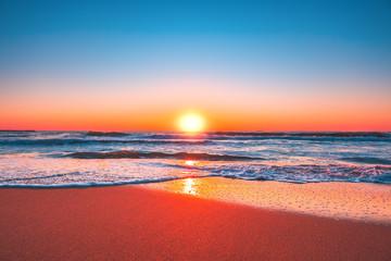 Fototapeta Wschód / zachód słońca Beach sunrise or sunset with clear blue sky and rising sun