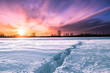 Scenic View Of Frozen Land Against Dramatic Sky During Sunset