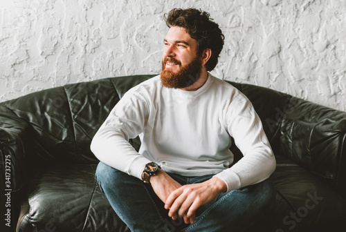 Fotografía Portrait of handsome bearded man looking away and sitting on sofa