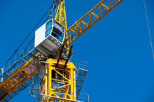 Iron Cabin Of A Yellow Tower Crane On A Blue Sky Background Close-up