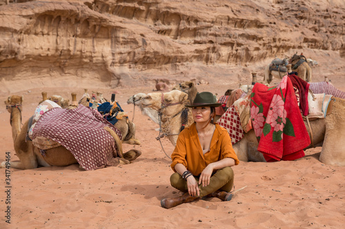 A camel driver in a cowboy hat and boots sits in Turkish on the sand in the desert amid a herd and rocky cliffs Fototapeta