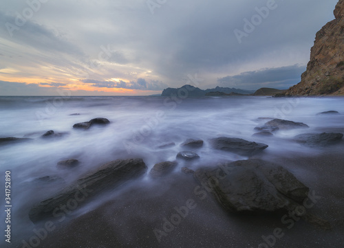 Seascape with stones ashore mountains on the horizon and gray sky Canvas Print