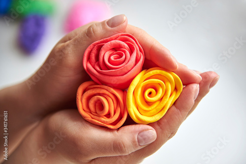 Photo Delicate roses made of super light airy colored plasticine in the hands of a woman