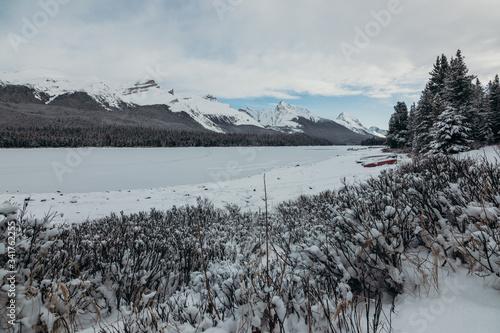 Fotografía Lago helado con montañas y árboles en invierno