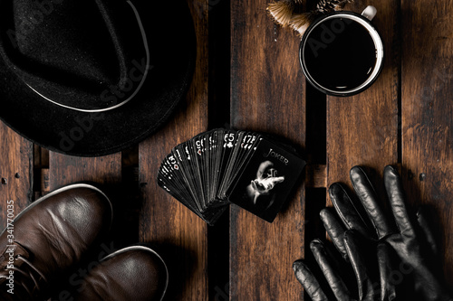 Valokuvatapetti cowboy boots , leather gloves, coffee cup, playing cards and hat on a wooden table