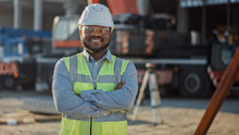 Portrait Of Contractor / Investor / Architectural Engineer Wearing Hard Hat And Safety Vest Standing On A Commercial Building Construction Site, Crosses Arms Confidently. In Background Crane Machinery