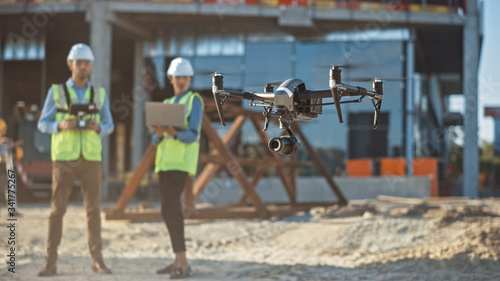 Obraz Diverse Team of Specialists Pilot Drone on Construction Site. Architectural Engineer and Safety Engineering Inspector Fly Drone on Commercial Building Construction Site Controlling Design and Quality - fototapety do salonu