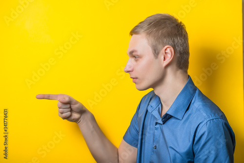 Young men threatens someone - isolated on yellow background Wallpaper Mural