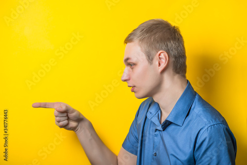 Young blond man in a blue shirt on a yellow fone Canvas Print