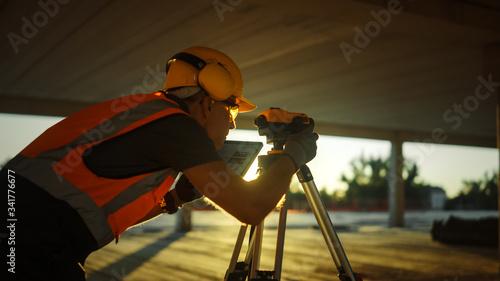 Obraz na plátně Inside of the Commercial / Industrial Building Construction Site: Engineer Surveyor Takes Measures with Theodolite, Using Digital Tablet Computer