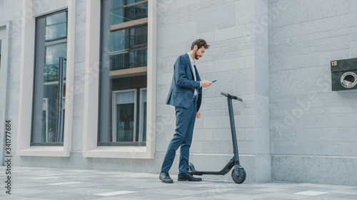 Businessman in a Suit is Activating an Electric Scooter with a Smartphone Canvas Print